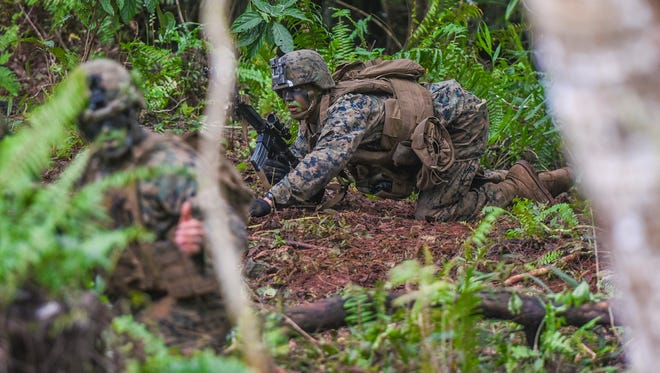 In this Nov. 7 file photos, Marines prepare to conduct a mock assault to demonstrate their ability to gain control of an abandoned building at Andersen South in Yigo.