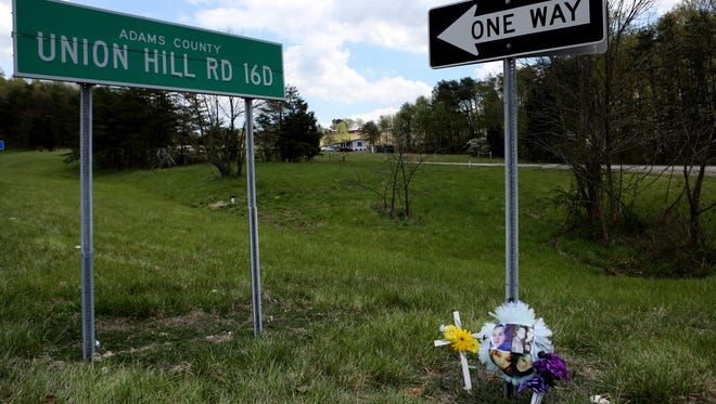 A memorial sits near Union Hill Rd, on Monday afternoon, where eight members of the Rhoden family were found shot and killed in their homes on Friday morning.