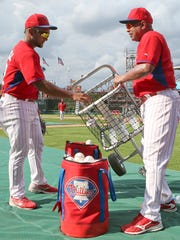 Phillies bullpen catchers Jose Mayorga (left) and Jesus Tiamo work at the end of batting practice before a game at Citizens Bank Park on Friday.