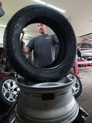 Courtney Sammak, an auto technician at Furr's Tire Service in Dover, prepares a new tire for installation. Furr's is among several hundred businesses that are now required to obtain a state permit for their scrap tire facilities, but one of only a handful who have done so.