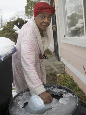 Fayette Coleman uses a knife to chip through ice during a cold spell last month. The former factory worker who has health problems has lived without running water since 2013.