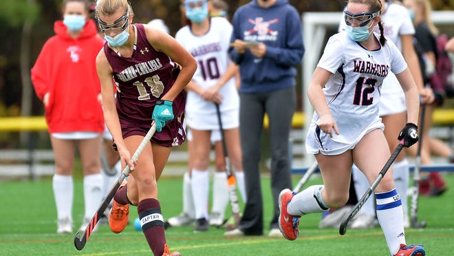 Concord-Carlisle's Emily Stone moves the ball upfield as Lincoln-Sudbury's Sarah Molloy (right) gives chase on Oct. 24, 2020. Molloy plans on playing field hockey at Kenyon College next fall.