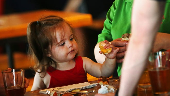 McKenna Rowe, 1, enjoys snacks at the new Sun King tap room in Fishers, Ind., Monday, June 29, 2015, which is a child-friendly facility.