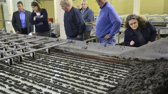 Members of the St. Cloud City Council and Public Services Director Pat Shea (left) look over a machine that removes water from solid waste during a tour in 2014 of the St. Cloud Wastewater Treatment Facility.