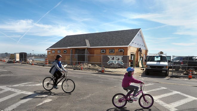 Bicyclists ride along Long Beach Avenue in York, Maine, in 2018, as construction work on the new bathhouse was underway.