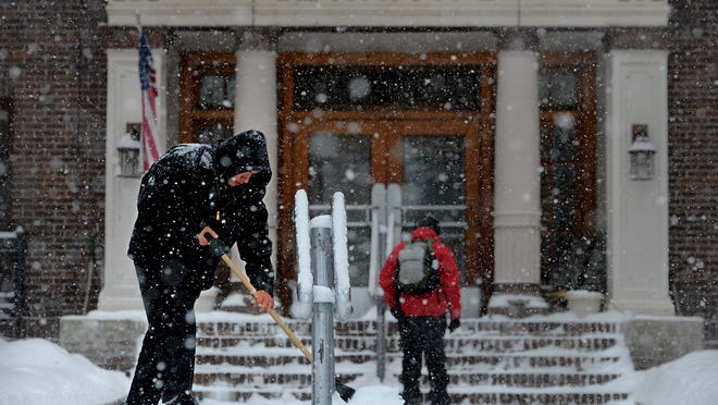 Cody Charboneau shovels the walkway in front of the Blackstone building in downtown Great Falls during Monday's snowstorm.