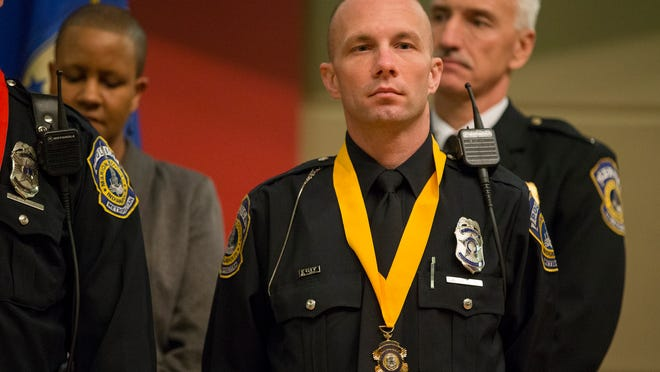 Nicholas Gallico, stands with his Medal of Honor award, earned on the night officer Perry Renn was killed in the line of duty, Indianapolis Metropolitan Police Department Honor Awards, Central Library, Indianapolis, Friday, Nov. 7, 2014.