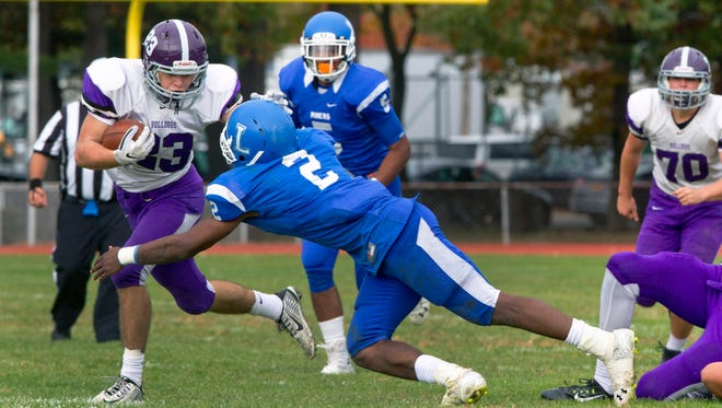 Rumson's Matt Vecchiarelli tries to escape the grip of Lakewood's Amir Tyler during Rumson-Fair Haven Football vs Lakewood in Lakewood,  NJ on October 24, 2015