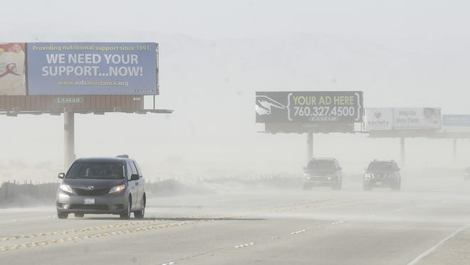 A car emerges from heavy windblown sand ahead of two other cars made nearly invisible on Gene Autry Trail, north of Vista Chino, in Palm Springs.