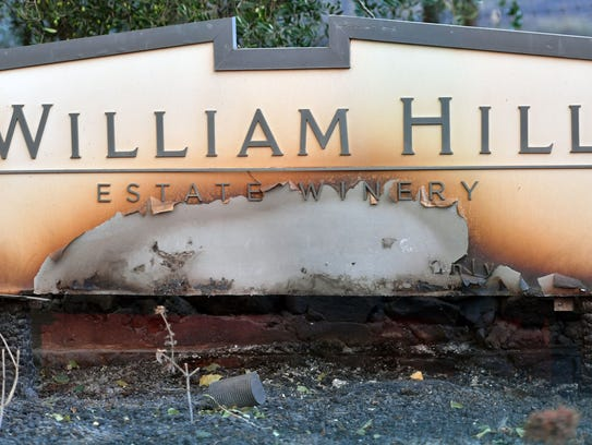 A partially burned sign is seen amidst smoldering remains
