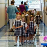 Students wait in the hall while moving from class to an activity on the first day of school at Sacred Heart.