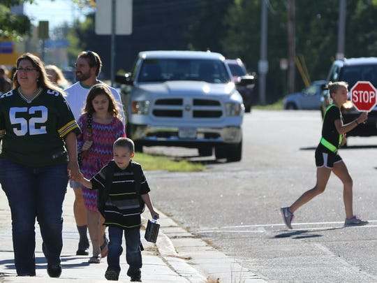 Families approach Madison Elementary School on the first day of classes as student crossing guards help direct traffic.
