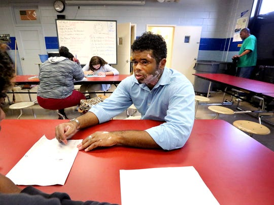 Marcus Lucas II works one-on-one with Ray'quwan Sweet, on of his Spanish students in the cafeteria of Holloway High School on Wednesday Sept. 14, 2016. The cafeteria has to serve both as a lunchroom and a classroom because of overcrowding. Holloway High School custodian Thomas Hardison works quickly in the background to clean up the cafeteria so that class can resume.
