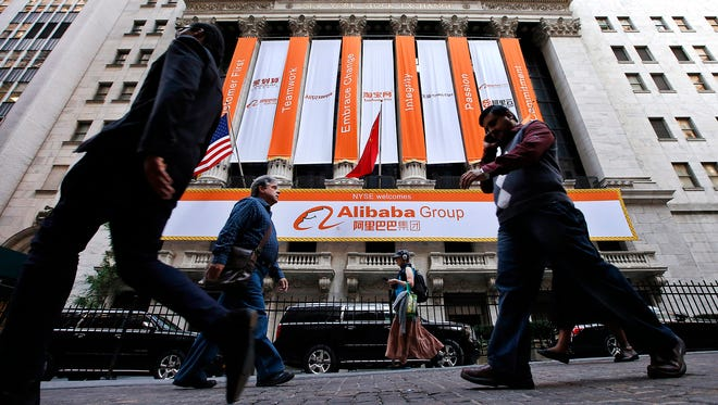 Pedestrians pass by the New York Stock Exchange on the day of Alibaba's initial public offering, Sept. 19, 2014, in New York.