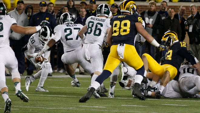 Michigan State's Jalen Watts-Jackson (No. 20) recovers the muffed punt by Michigan punter Blake O'Neill (No. 12) and runs it back as the clock runs out for State's game winning touchdown and a 27-23 win on Saturday, October 17, 2015, in Ann Arbor.
