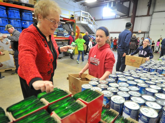 Employee Sue Kersemeier, left, fills Evergreen Elementary School student Abby Sendeleach's carton Thursday at K-tech Kleening Systems in Weston. About 90 local elementary school students volunteered to package foods for needy families. The food was delivered on Sunday.