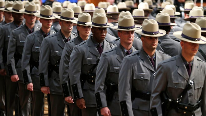 Some of the nearly 170 graduating troopers march into the Empire State Plaza Convention Center during the New York State Police 201st Session graduation ceremony on Thursday, July 17, 2014, in Albany, N.Y. (AP Photo/Mike Groll)