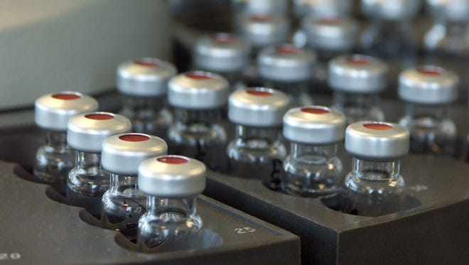 A gas chromatography autosampler loaded with sample vials with the front left vials selectively in focus.
