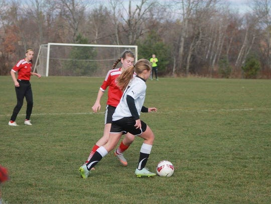 Kelsie Kostuchowski maneuvers around a defender in