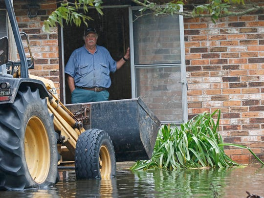 Thomas Foreman looks out past the bulldozer he is using to empty the flood-soiled carpeting from his home in the small community of Iowa, La., on Aug. 30, 2017.
