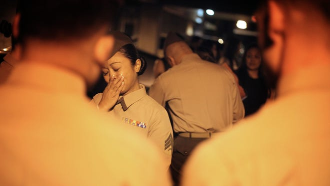 A Marine who served with Cpl. Allan DeVillena II starts to cry upon hearing DeVillena's grandmother weeping during a candlelight vigil for the Marine who was fatally shot by Palm Springs police in 2012.