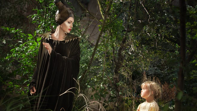 """This image released by Disney shows Angelina Jolie as Maleficent, left, in a scene with her daughter Vivienne Jolie-Pitt, portraying Young Aurora, in a scene from  """"Maleficent."""""""