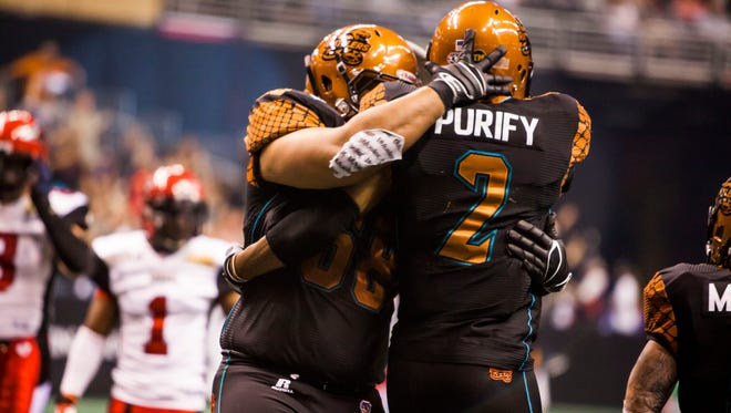 Players congratulate Rattlers Maurice Purify (2) after a touch down during the Jacksonville Sharks and Arizona Rattlers arena football game on Saturday, April 5, 2014 in Phoenix.