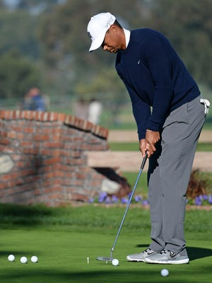 Tiger Woods practices on the putting green before the first round of the Farmers Insurance Open golf tournament during a fog delay at Torrey Pines Municipal Golf Course.