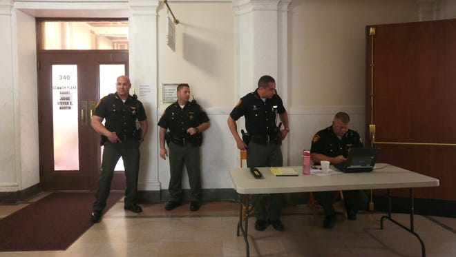 """Sheriff's deputies stand outside of Hamilton County Common Pleas Judge Steve Martin's courtroom early this month. Increased security measures are now being taken in response to deaths believed to be connected to witness intimidation. Deputies are positioned at the courtroom door to confiscate cellphones and """"wand"""" spectators."""