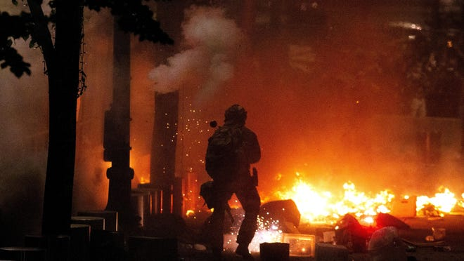 Federal law enforcement emerge from the Mark O. Hatfield United States Courthouse as fires burned during a protest in Portland, Ore., Wednesday, July 22, 2020. With the deployment by President Donald Trump of militarized federal agents in early July, the protesters now number in the thousands, showing up nightly. (Beth Nakamura/The Oregonian via AP)