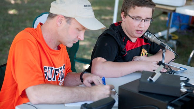 Sunfield residents Brian Wellwood and his son Andrew, 14, participate in the Amateur Radio Operator Field Day on Saturday, June 25, 2016 at Rayner Park in Mason.