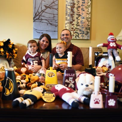 Jamie and Scott Martin sit with their children James Harris and Mary Ann at their home filled with Southern Miss and Mississippi State items. Scott graduated from Mississippi State and Jamie graduated from Southern Miss.