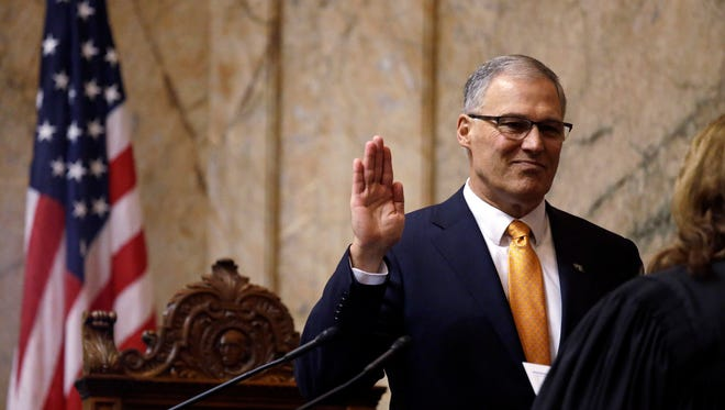 Gov. Jay Inslee takes the oath of office before his inaugural address to a joint session of the Legislature as he begins his second term Wednesday in Olympia.