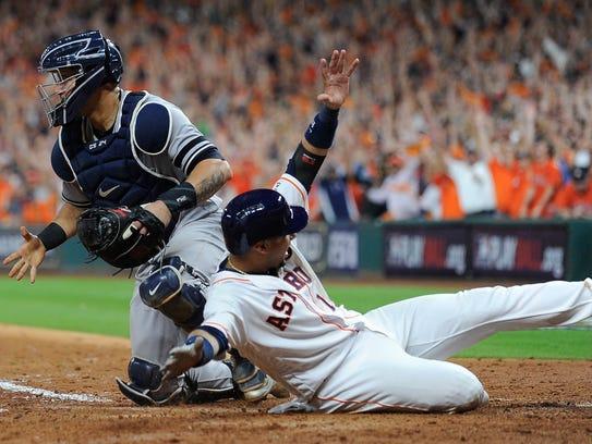 Houston Astros' Yuli Gurriel slides safely past New