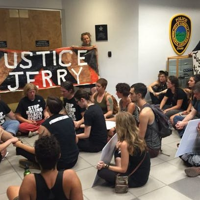 Protesters occupy the lobby of the Asheville Police Department during a protest calling for justice in the wake of an officer-involved shooting that left a black man dead.