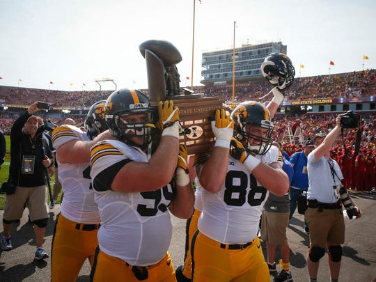 Members of the Iowa Hawkeyes football team carry off the Cy-Hawk Trophy after a 44-41 win over Iowa State on Saturday, Sept. 9, 2017, at Jack Trice Stadium in Ames, Iowa.