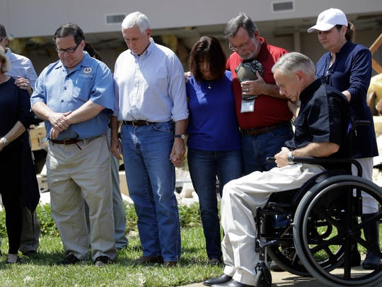 Vice President Mike Pence, center, holds the hand of