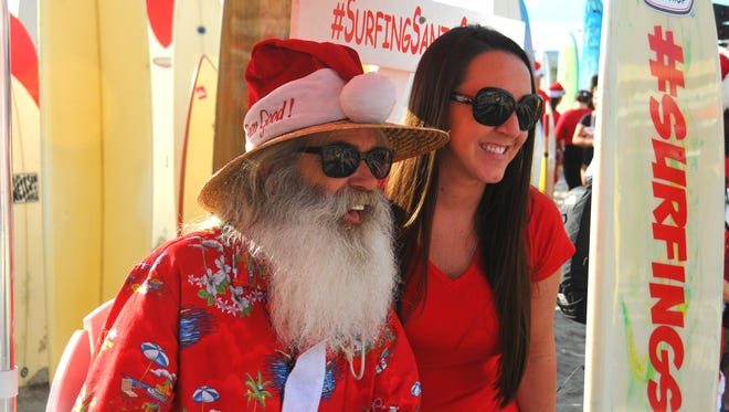 FILE - Thousands turned out to attend the annual Surfing Santas event in Cocoa Beach on Saturday, Dec. 24, 2016. The National Weather Service recorded a high temperature of 81 degrees.