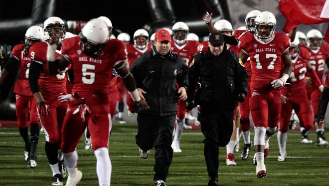 FILE - Coach Pete Lembo (middle) runs out to the field with Ball State players Nov. 6 against Central Michigan.