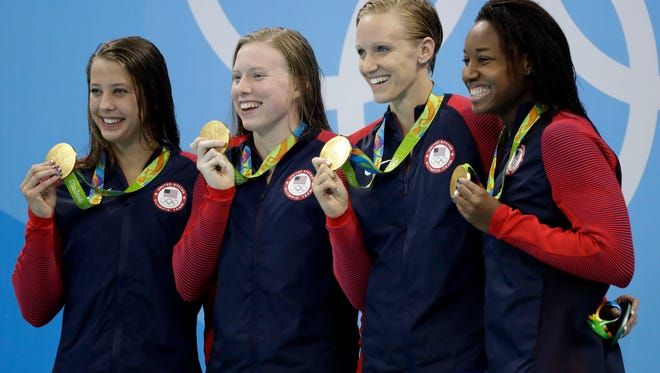 From left to right, United States' Kathleen Baker, Lilly King, Dana Vollmer and Simone Manuel display their gold medals for the women's 4 x 100-meter medley relay final during the swimming competitions at the 2016 Summer Olympics, Saturday, Aug. 13, 2016, in Rio de Janeiro, Brazil. (AP Photo/Rebecca Blackwell)