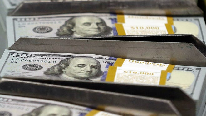 In this 2013 photo, freshly-cut stacks of $100 bills make their way down the line at the Bureau of Engraving and Printing Western Currency Facility in Fort Worth, Texas.