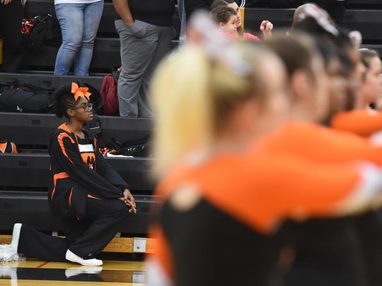 Northeastern cheerleader Ajani Powell takes a knee during the national anthem before a boys' basketball game at Red Lion.