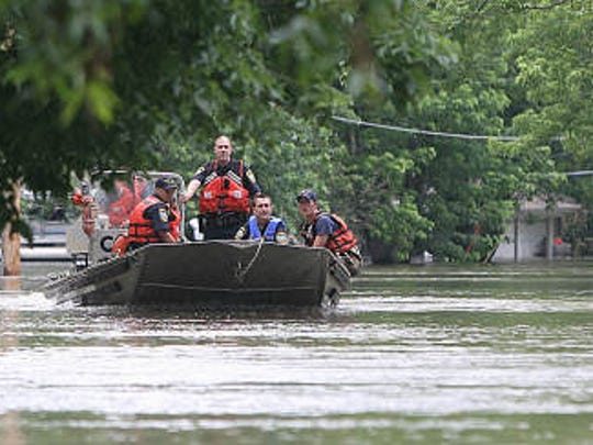 Members of the Iowa City Police and the Coast Guard patrol the neighborhood along Normandy Drive in Iowa City on Sunday, June 15, 2008.