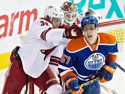 Arizona Coyotes' Brandon Gormley (33) cross-checks Edmonton Oilers' David Perron (57) as goalie Devan Dubnyk (40) looks for the puck during the second period of an NHL hockey game in Edmonton, Alberta, Tuesday, Dec. 23, 2014. (AP Photo/The Canadian Press, Jason Franson)