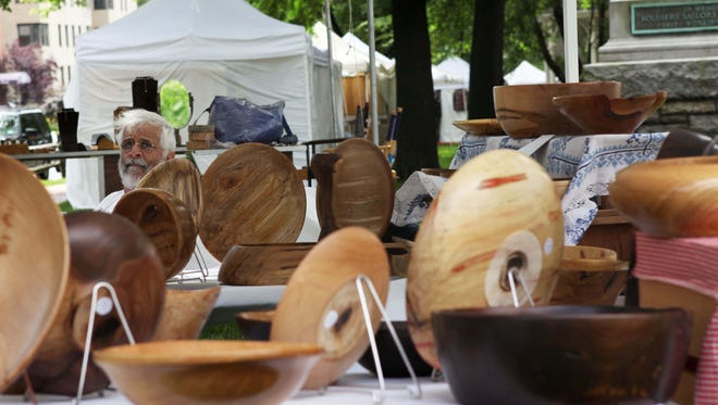 Charles Lazarus of Kitchawan, who creates works out of reclaimed New York wood for his business The Misshapened Bowl, sits at his tent at the White Plains 50th Annual Outdoor Arts Festival at Tibbits Park in White Plains on June 2, 2012.