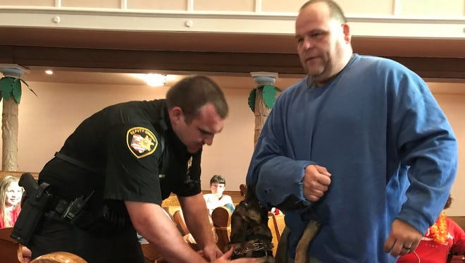Dep. Steve Mox and his dog Chili demonstrate how they would bit and apprehend a subject with Det. Dave Stone wearing a bite sleeve to students and volunteers at a Vacation Bible School Thursday at Grace United Methodist Church.