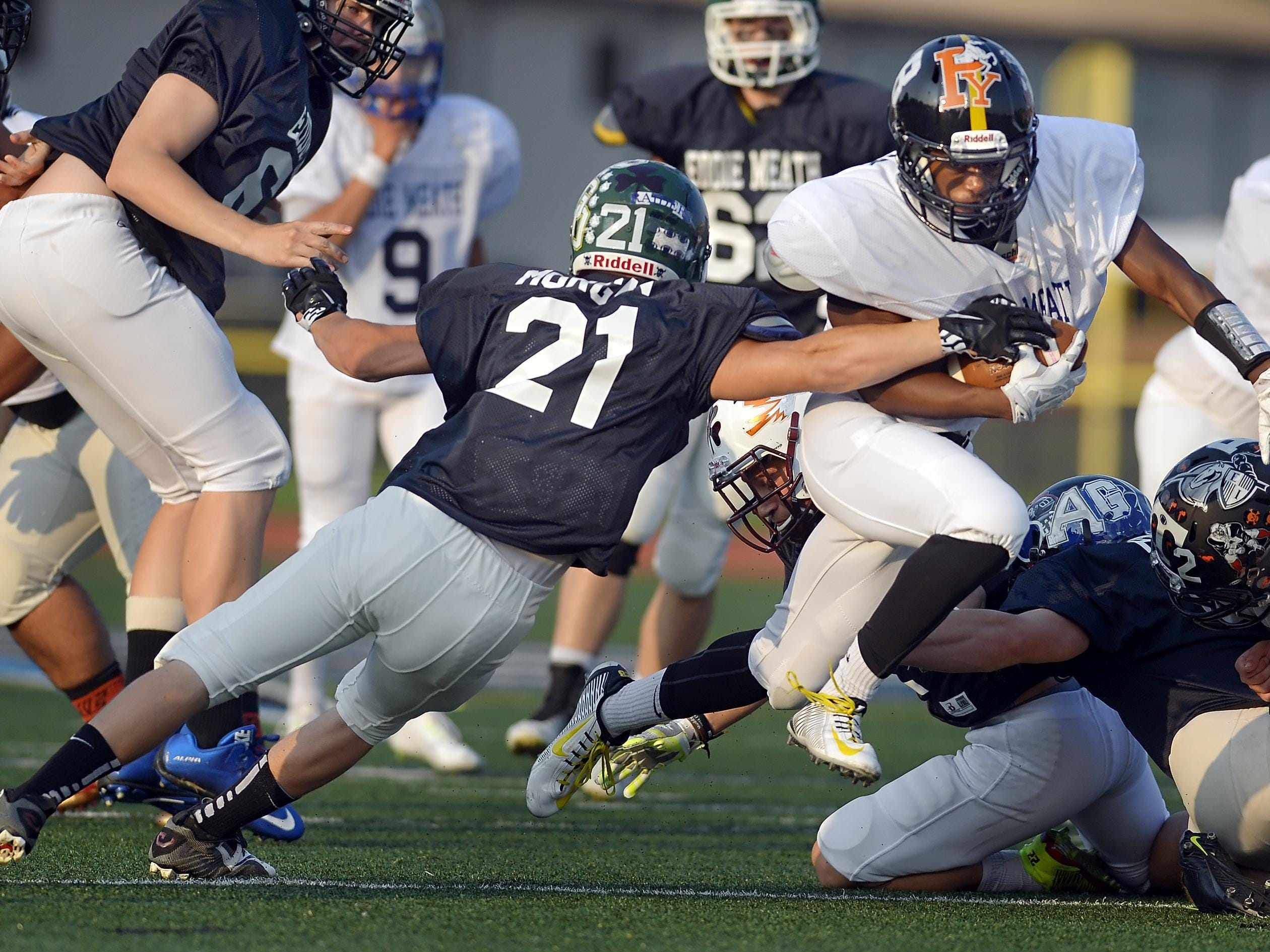 McQuaid's Amari Lawrence, right, avoids the tackle of Greece Olympia's Ryan Morgan during the 33rd Annual Eddie Meath All-Star Game played at Eastridge High School on Saturday, July 11, 2015.