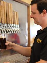 Matt McMillan pours one of Hexagon Brewing Co.'s own brews.