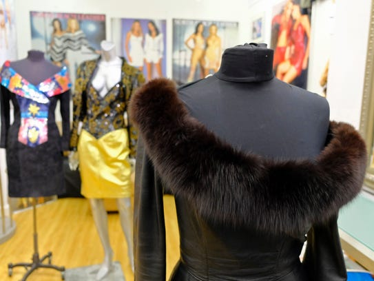 A dress with a fox fur collar is displayed in the basement
