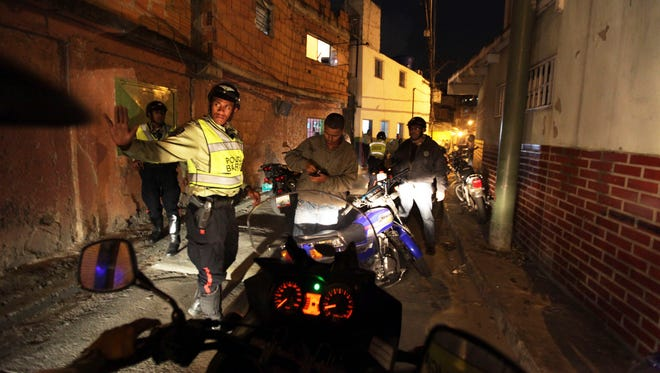 In this photo taken Friday, June 1, 2012, Baruta municipal police officers check the identification of a man while on a night patrol in Caracas, Venezuela.